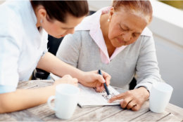 Caregiver assisting old woman to write