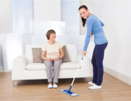 Caregiver cleaning the house of old woman