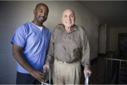 Caregiver assisting old man to walk