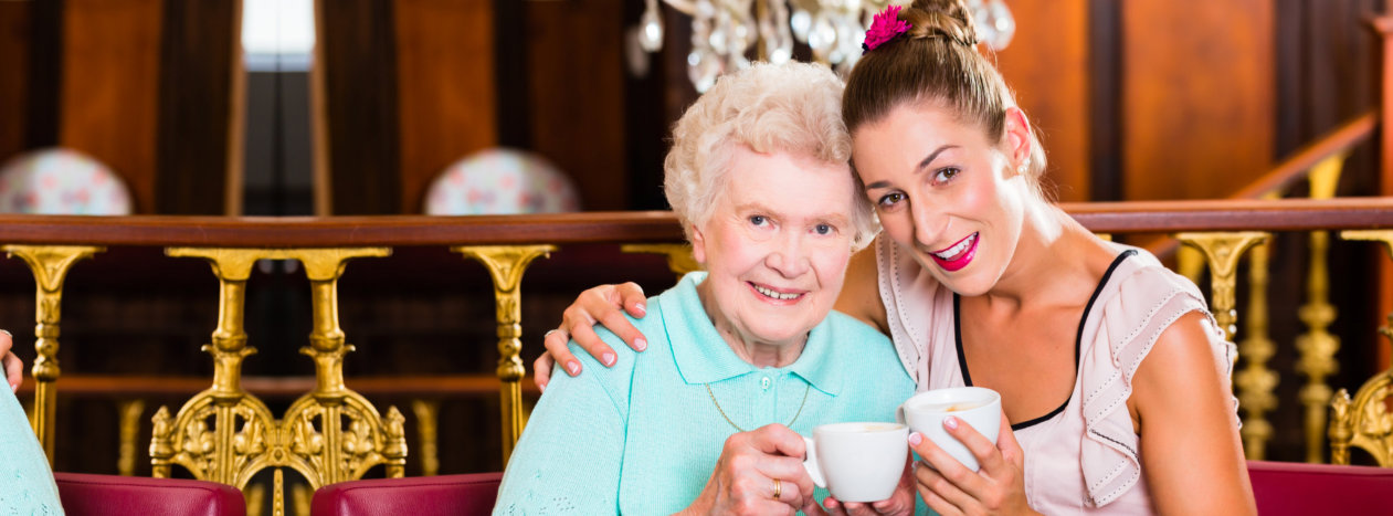 Old woman is drinking tea with her caregiver